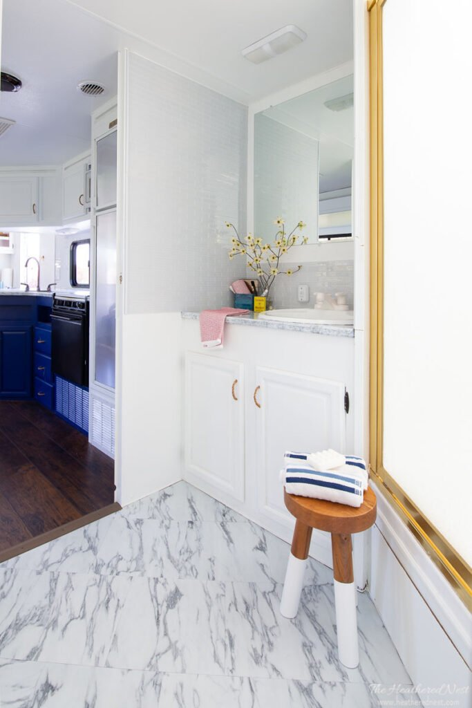 AFTER DIY bathroom renovation in a travel trailer with board and batten walls, blue and white wallpaper, nautical accessories with red, white and blue motif