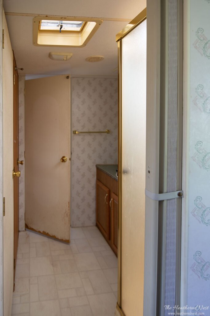 BEFORE shot of a travel trailer DIY bathroom renovation with green laminate counters, brass corner shower, 1990s wallpaper, brass fixtures and clunky medicine cabinet