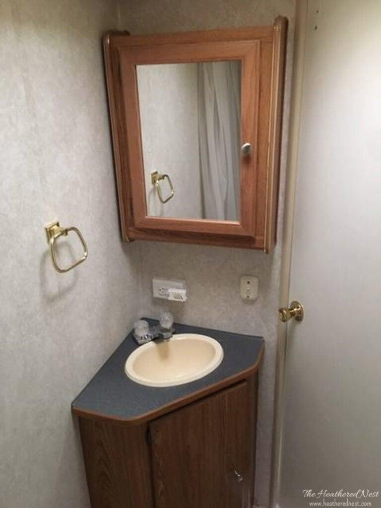 BEFORE shot of a travel trailer DIY bathroom renovation with corner sink, laminate countertop, small medicine cabinet