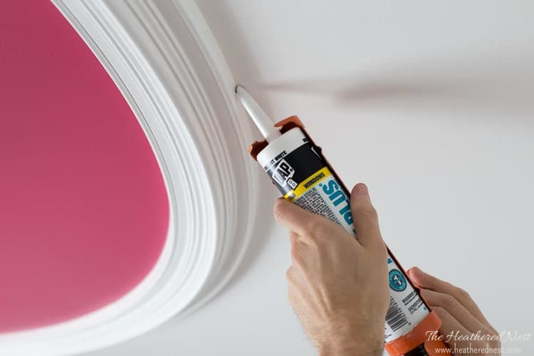 caulking a white ceiling ring/medallion into place