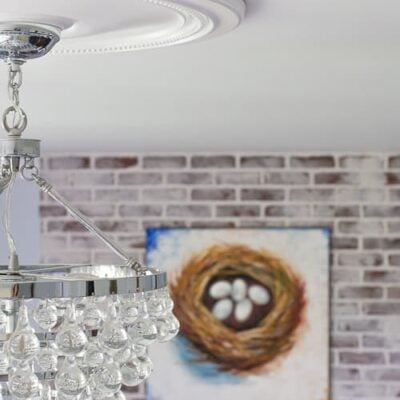 A close up of a glass teardrop chandelier, with Ceiling medallion/small ceiling ring