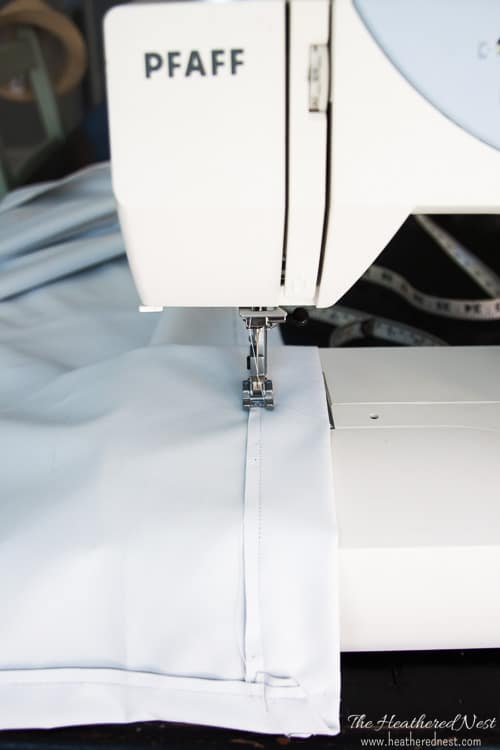 Sewing edges of blackout material to create a quick and easy DIY outdoor movie screen. If you don't sew, use fusion tape or fabric glue.