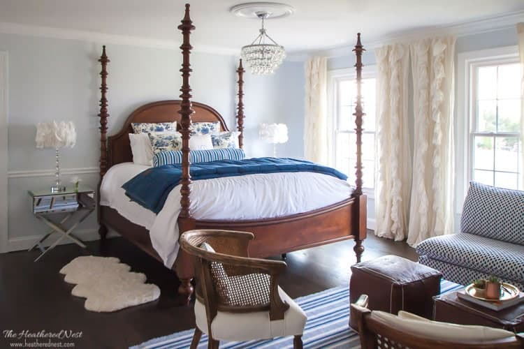 Light blue bedroom with four poster bed, crystal chandelier, sheepskin rug, mirror end tables