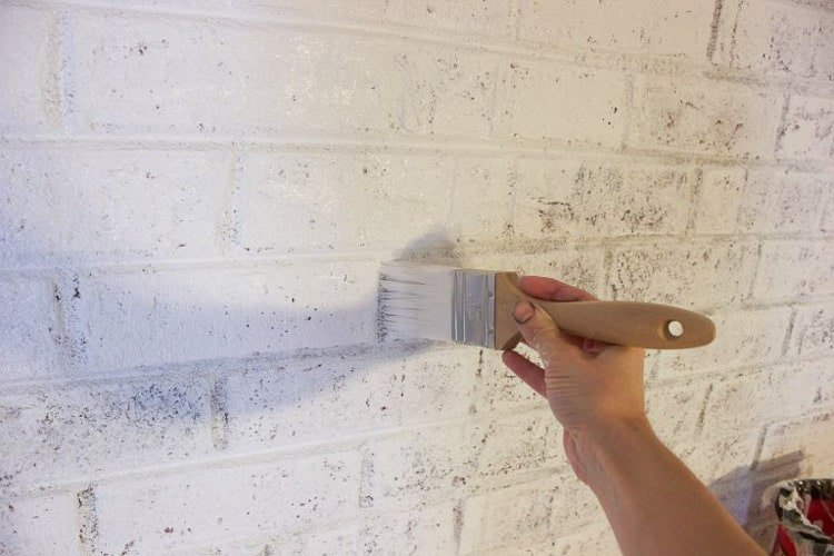 paintbrush with white paint shown painting a brick fireplace
