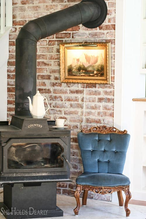 brick veneer on a rustic accent wall behind pot-bellied stove