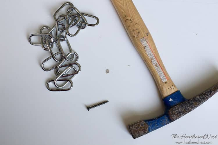 Paint Touch Up for Your Ikea Furniture: hammer, chain and a screw lying on a white IKEA shelf