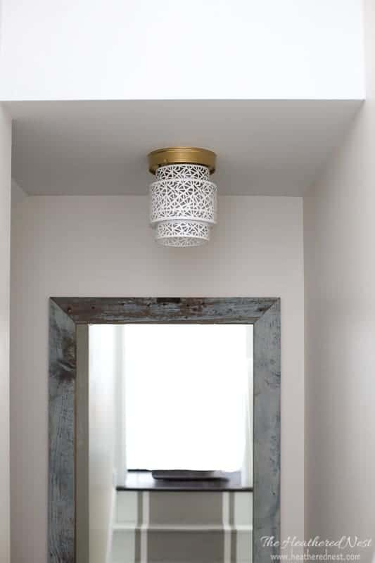 Easy Ceiling Light Shades: Unbelievable...and what a great idea for renters, too! Try this 5-minute, NO TOOLS needed boob light makeover using a woven basket from the Heathered Nest! Amazing way to update that dated flush mount ceiling lighting! #DIY #lighting #homehack #booblight #DIYlighting