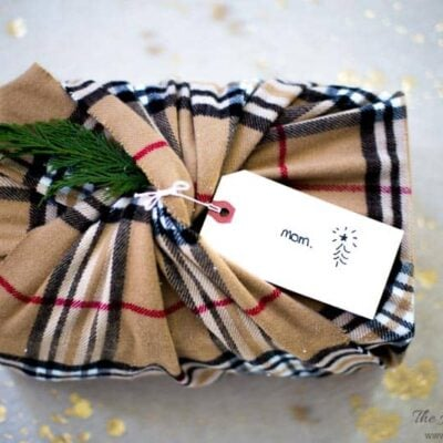 winter scarf eco-friendly gift wrap idea with plaid scarf and large manilla tag on wrapped gift