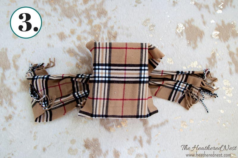 continued process for wrapping a box in a winter scarf for an eco-friendly gift wrapping idea