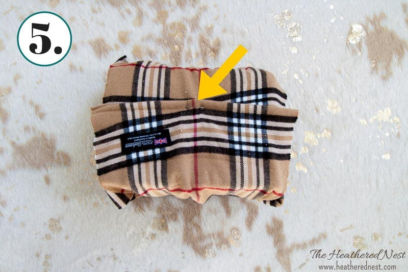 pinning the winter scarf with a safety pin to secure in place for eco-friendly gift wrap idea