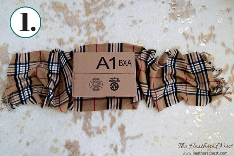 box sitting atop a plaid winter scarf