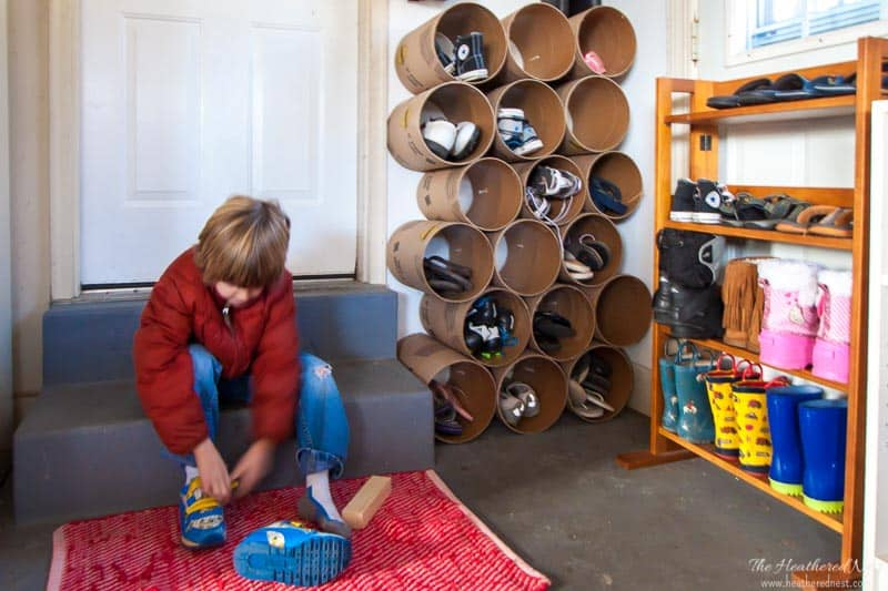 completed shoe cubby in garage. little boy putting on shoes next to completed unit made from concreted form tubes
