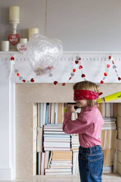 This is the easiest DIY piñata I've ever seen! What a cute DIY Valentine's Day idea for the kids! Make this heart-shaped piñata in 10-minutes. #DIYpiñata #easypiñata #heartpiñata #valentinecraftforkids #kidscrafts