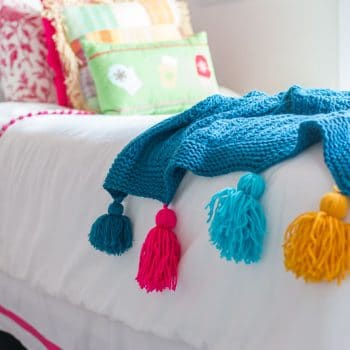 ADORABLE! And super easy DIY project. DIY tassel tutorial. Add tassels to any throw in minutes. #DIYtassel #DIYtasselthrow #tasselthrow #DIYtassels #tasseltutorial