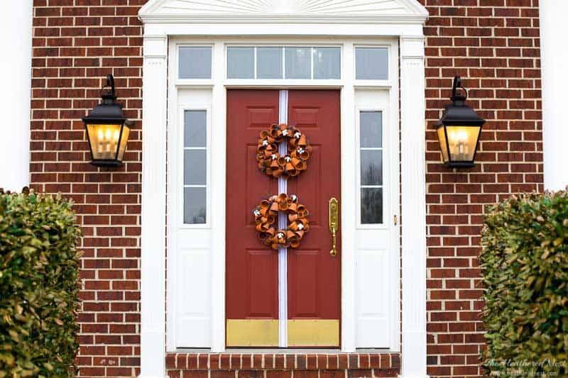 Welcome Spring In Style With This Beautiful DIY Terra Cotta Clay Pot Wreath! Image of red front door with double hung clay pot wreaths and a ribbon runner.
