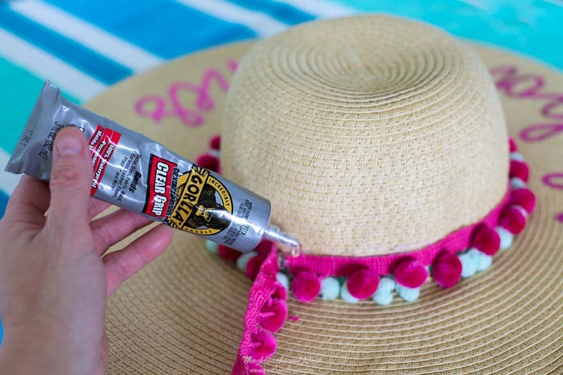 Adding Gorilla Glue Clear Grip to adhere pom pom trim to beach hat for summer! Add a pop of color and fun to your floppy wide brim beach hat this summer with pom pom trim, or fringe! It will take less than 5 minutes! #beachhat #pompomtrim #widebrimhat #floppyhat #embellishedhat #beachhatDIYsummer #beachhatDIYfun #pompomcrafts
