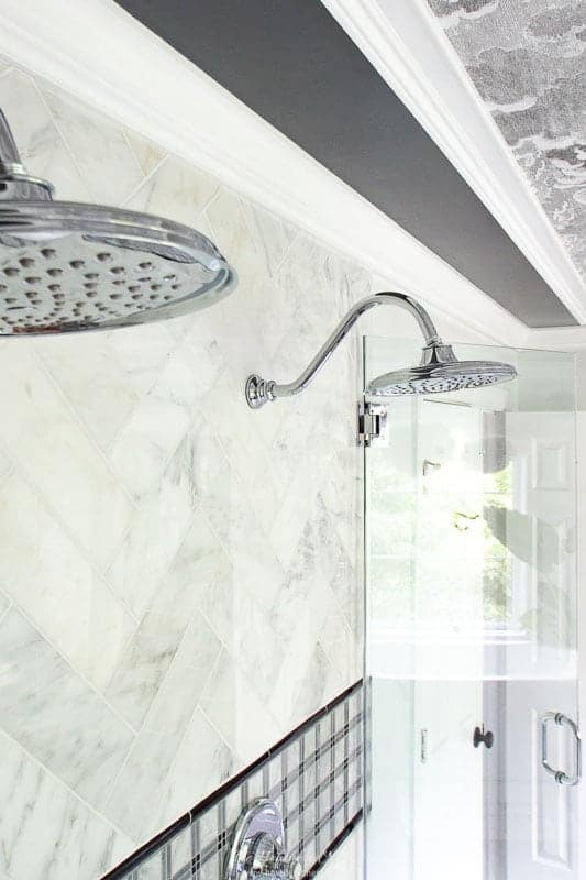 dual Moen showerheads in grey bathroom remodel with marble subway tile and frameless glass enclosure