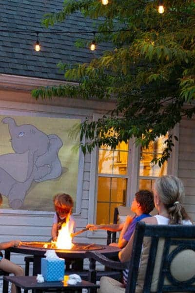 family watching movie on a DIY outdoor movie screen at home with a campfire