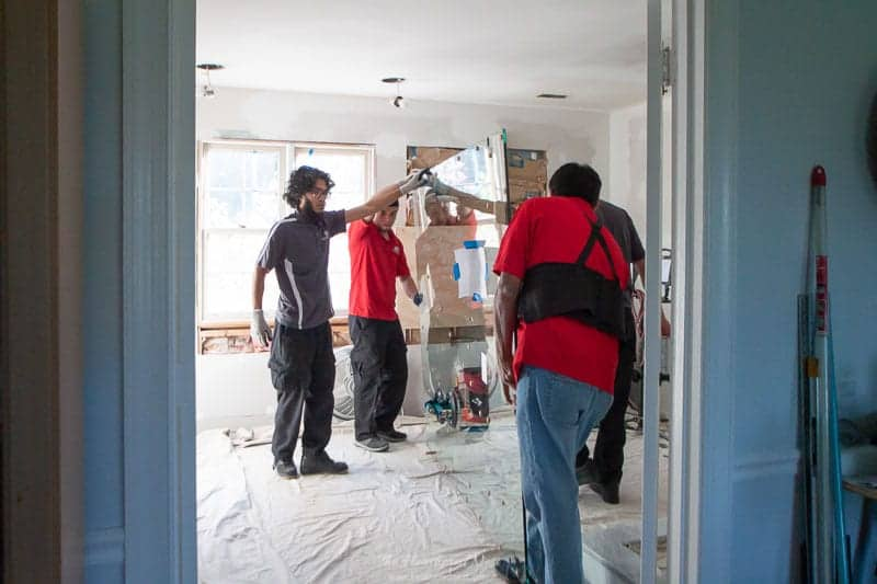 Glass for frameless glass shower enclosure being brought into the new space by team.