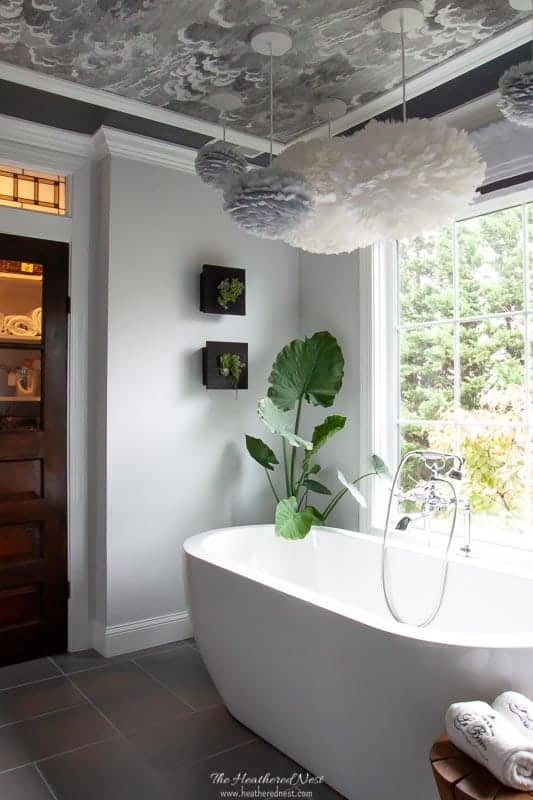 Check out this GORGEOUS #masterbathroom #renovation !! AMAZING from top to bottom. The #wallpaperedceiling the huge #picturewindows #modern #vesseltub #vintagedoor #walkinshower with #dulashowerheads ?! I'm in ❤️w/ this grey bathroom !! #doubleshowerheads #greybathroom #blackandwhitebathroom #masterbathroomideas #masterbathroomrenovation #DIY #fabriclooktile #greytile #graybathroom #luxurybathroomideas #cloudwallpaper #cole&son #livingwall #succulents #greenwall #verticalgarden