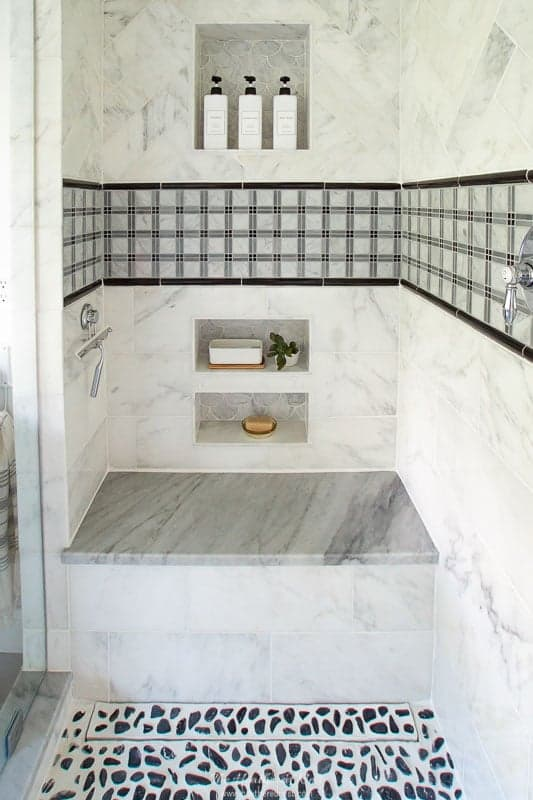 close up of tile work in DIY bathroom renovation / grey bathroom space / gray bathroom with black pebble tile and marble shower bench