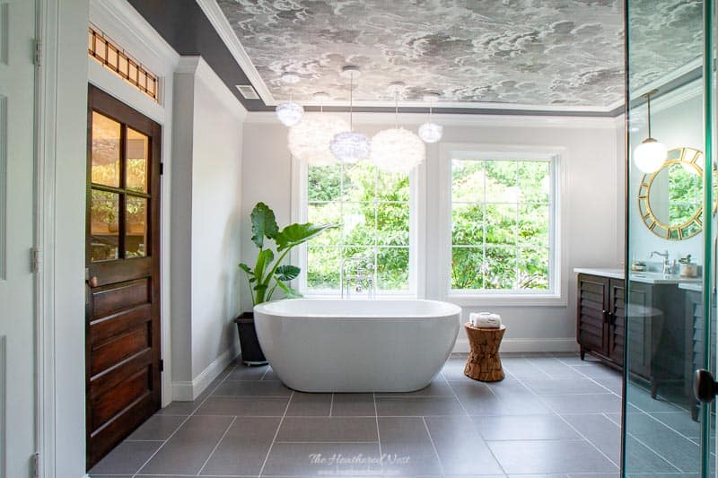 Check out this GORGEOUS #masterbathroom #renovation !! AMAZING from top to bottom. The #wallpaperedceiling the huge #picturewindows #modern #vesseltub #vintagedoor #walkinshower with #dulashowerheads ?! I'm in ❤️w/ this grey bathroom !! #doubleshowerheads #greybathroom #blackandwhitebathroom #masterbathroomideas #masterbathroomrenovation #DIY #fabriclooktile #greytile #graybathroom #luxurybathroomideas #cloudwallpaper #cole&son #moen #miseno #featherlights