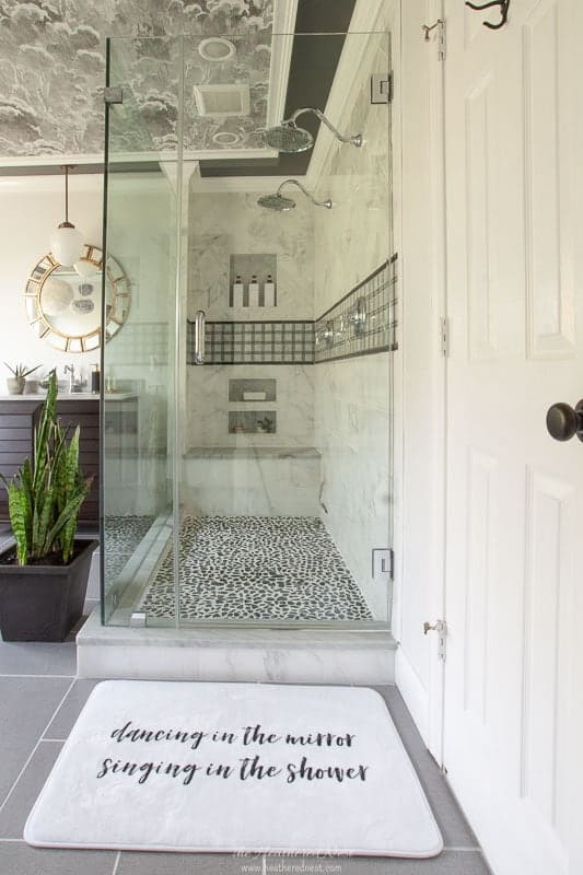 Completed shower with frameless glass enclosure in a grey bathroom with wallpaper on ceiling