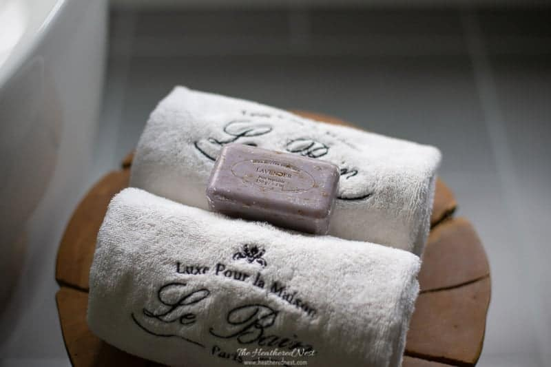 closeup of rolled towels and hand milled soap in grey bathroom reveal