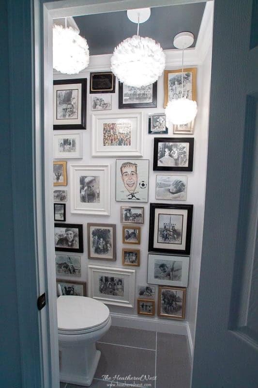 water closet with large gallery wall in grey bathroom with feather pendant lighting