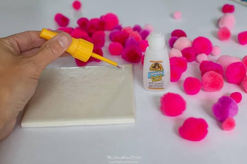 Use brush tip of Gorilla Glue Super Glue to pom poms to ceramic tile for DIY coasters