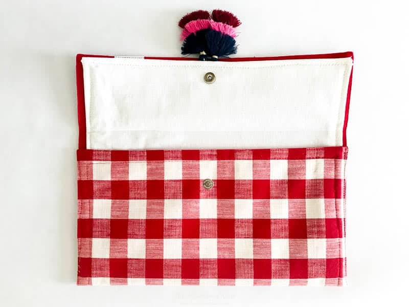 Adding tassels to this DIY red clutch bag is optional. Image of the buffalo plaid clutch with tri color tassels added.
