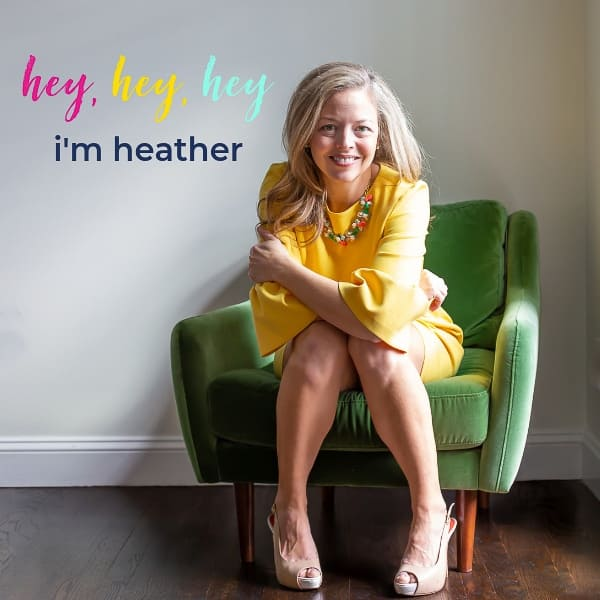 heathered nest owner, heather thibodeau wearing yellow dress seated in green velvet chair. text overlay, hey, hey, hey i'm heather
