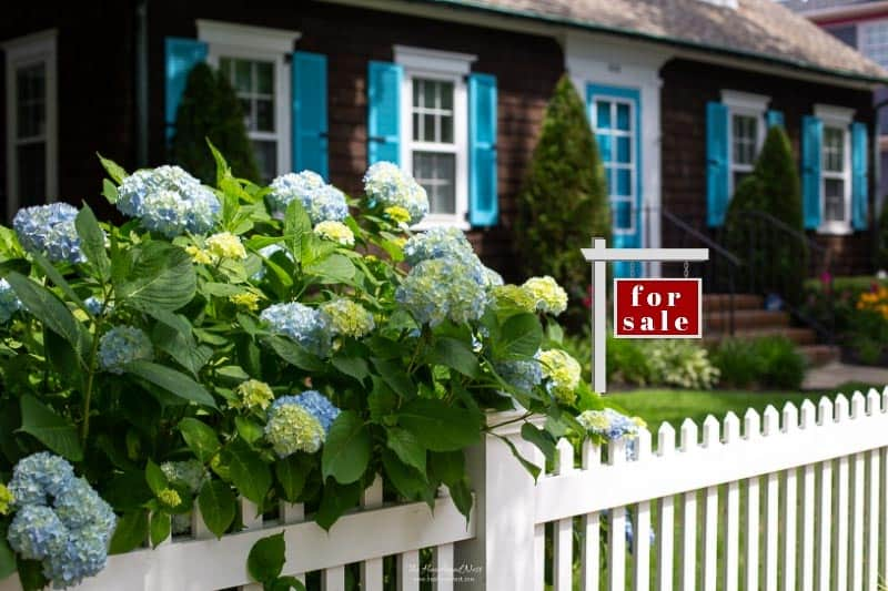 Cape Cod style home with white picket fence and for sale sign in yard. Tackling Clutter is always stressful. But it may be especially overwhelming when you're preparing to sell your home. Here are 5 Sure Fire Tips to Declutter & Get Your Home Sold! #howtodeclutter #decluttering #sellingyourhome #declutteringhomefeelingoverwhelmed #declutteringhometosell #declutteringhometoselltips #sellinghousetips
