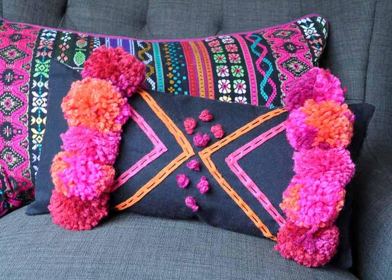 denim and geometric pom pom pillow