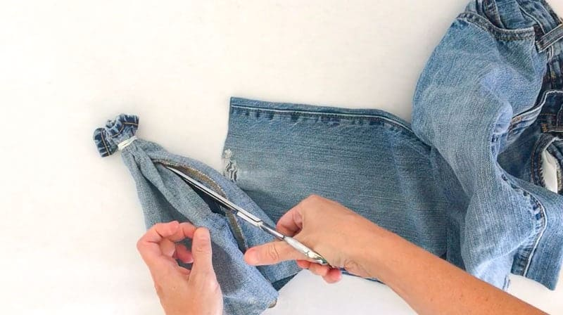cut slit in denim next to seam. one step in this easy fall craft making cute pumpkins from old jeans.