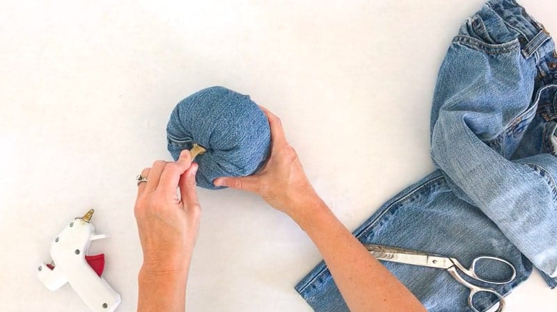 hot glue stem onto DIY denim pumpkin craft - an easy fall upcycling craft using old jeans.