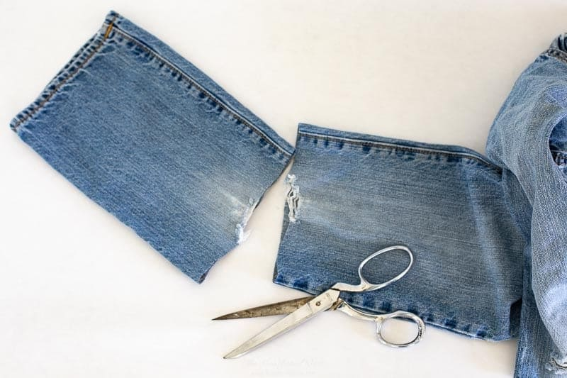 first step for this easy fall pumpkin craft is to cut a section of the old jeans leg off.