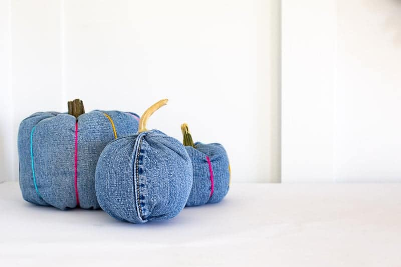 three denim pumpkins made from old jeans legs. takes 10-minutes without spines, or about 20 minutes with.
