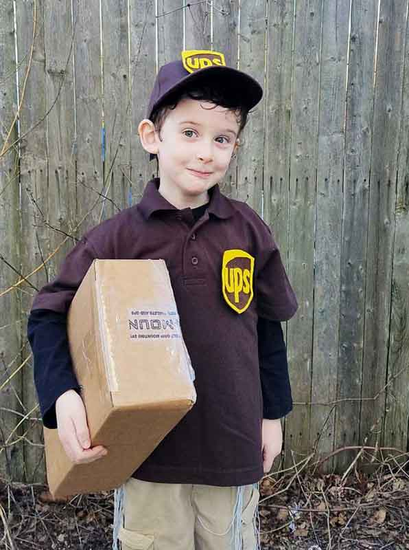 little boy holding cardboard box dressed up as a delivery man from UPS last minute halloween costume