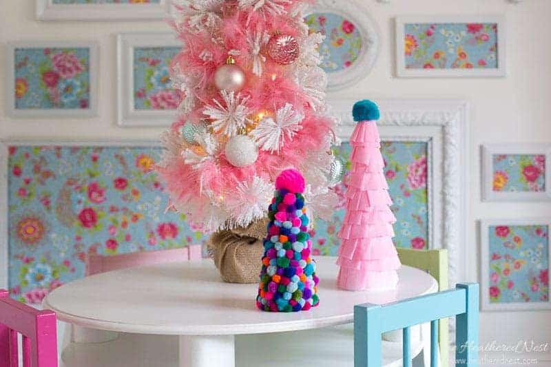 pom pom christmas tree on table next to crepe paper christmas tree