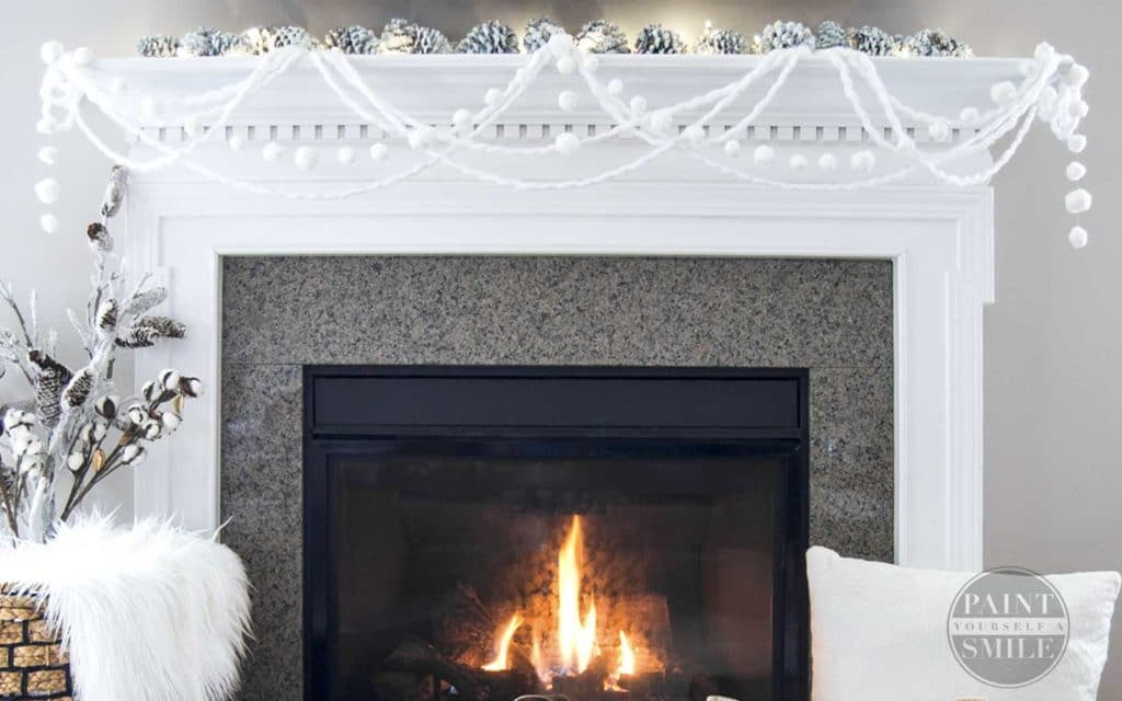 white pom pom garland hanging on a fireplace mantel