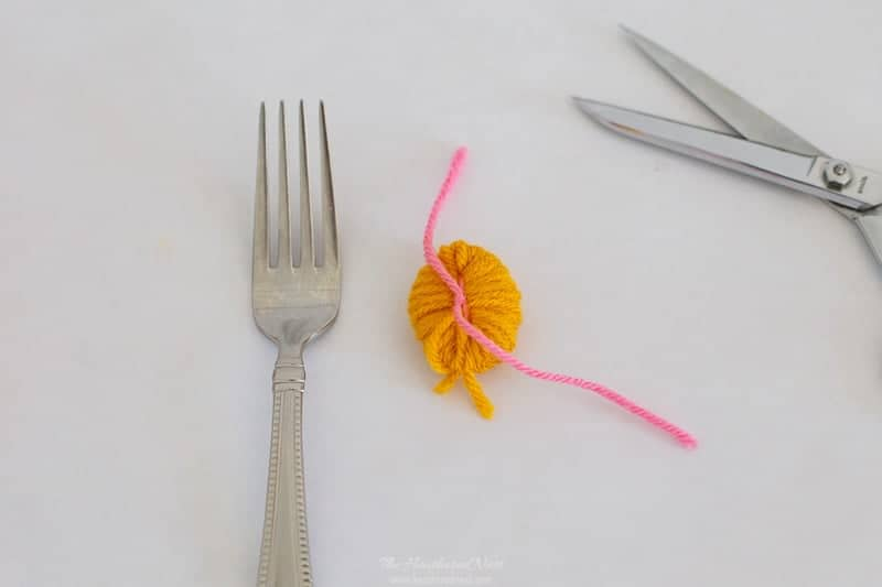 how to make pom poms with a fork. a simple step-by-step tutorial shows this easy pom-pom making method that takes less than 2-minutes per DIY pom pom craft! #howtomakepompomswithafork #DIYpompoms #pompomcrafts #easypompomcraft #yarnpompoms #howtomakepompomswithyarn #DIYpompomcrafts #howtomakepompomsstepbystep #howtomakepompomsvideo
