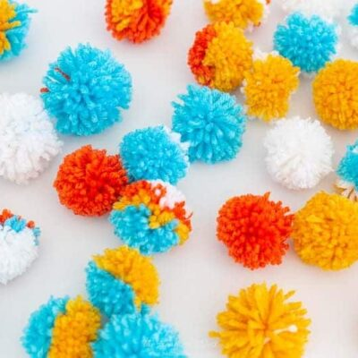 Lots of Colorful DIY Pom Poms on a White Background