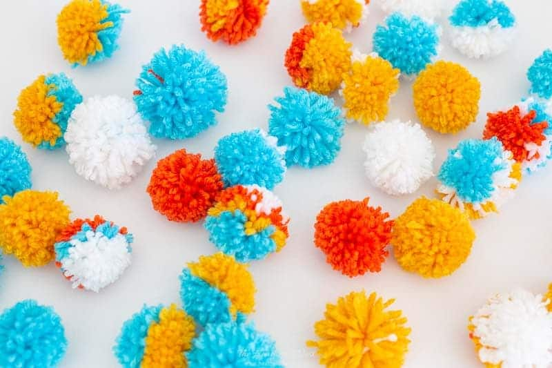 DIY pom poms are not hard to make. This is a bunch of DIY pom poms we made to use on our footstool makeover project.