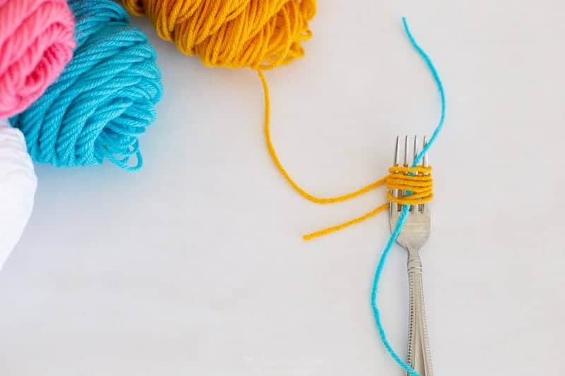 step 2 how to make pom poms with a fork: wrap fork with layers of yarn