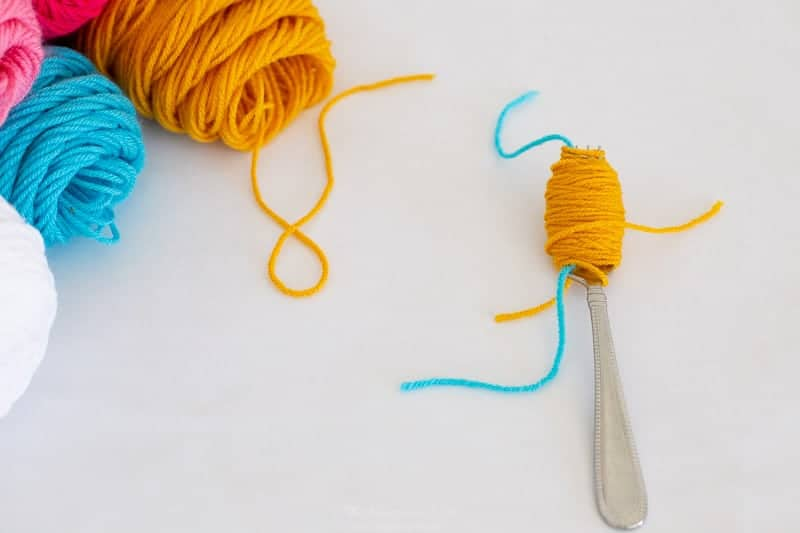 step 3 how to make pom poms with a fork. once wrapped about 30-50 times, snip end of yarn.