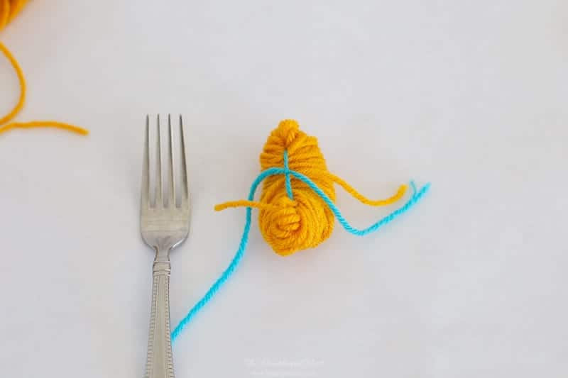 step 4 how to make pom poms with a fork: tie tight knot and slip off fork.