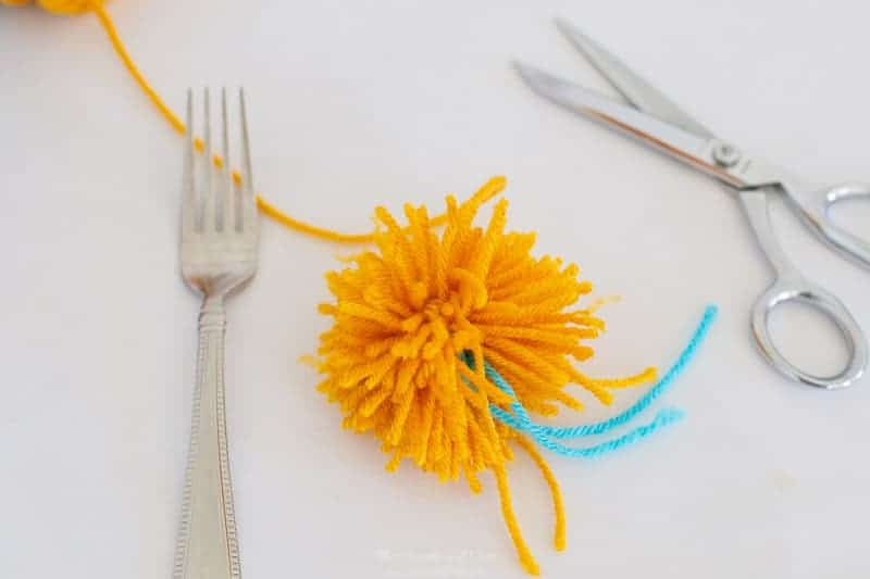 step 5 how to make pom poms with a fork: cut yarn loops.
