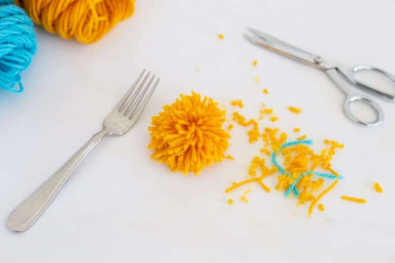 step 6 how to make pom poms with a fork: trim ends of yarn so all roughly uniform in length.