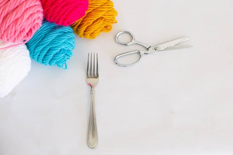 supplies needed for DIY pom poms with a fork include what is seen here: yarn, fork and scissors.